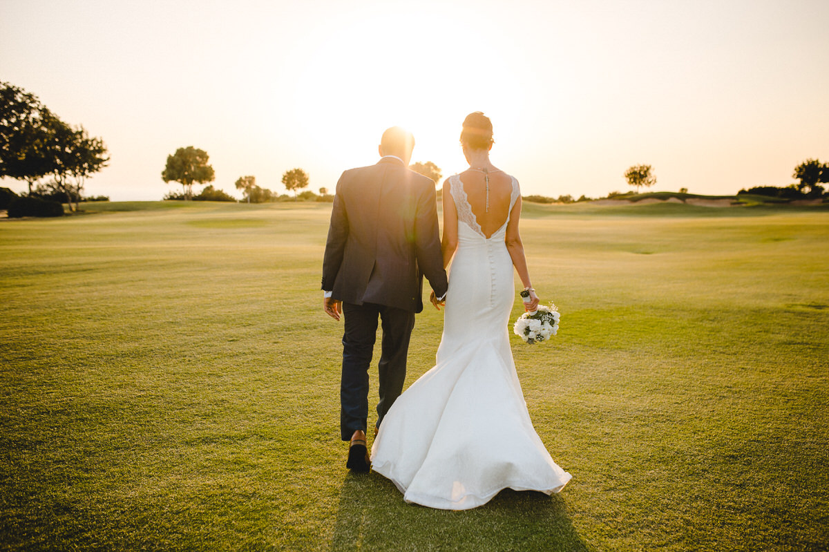 couple walking on golf course sunset