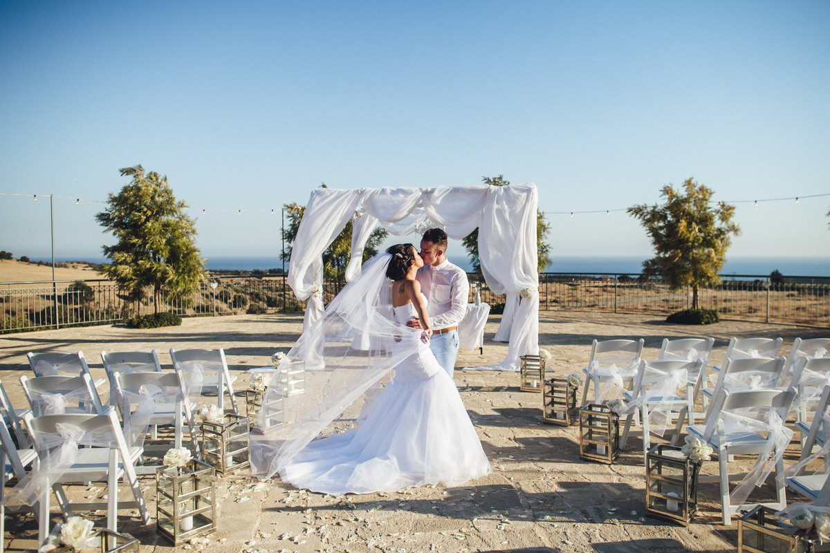 bride and groom kiss with sea in background
