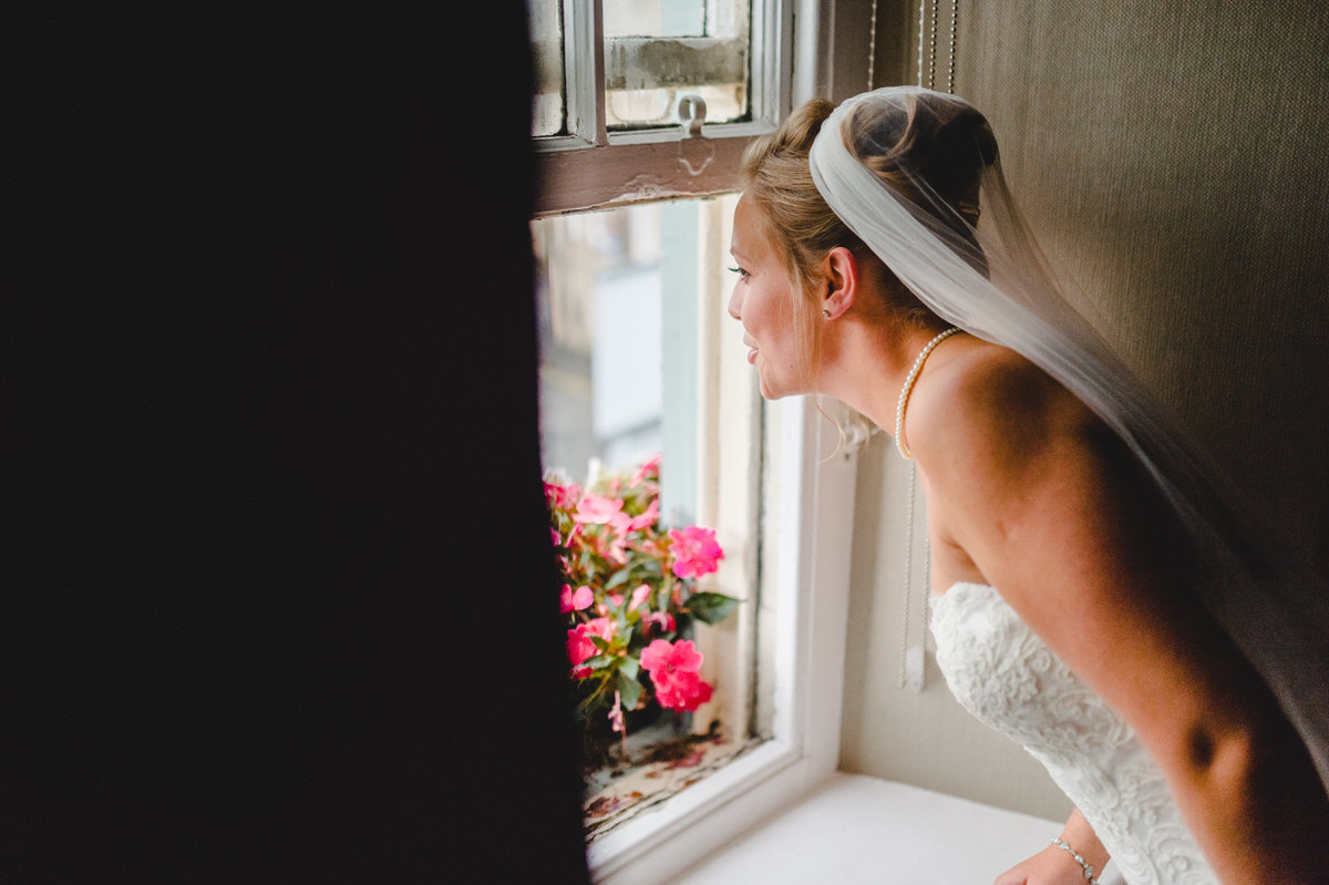 Bride looks through window at wedding car