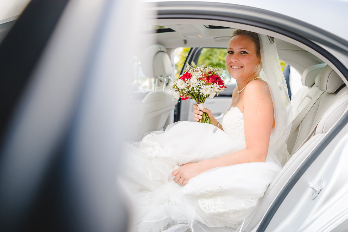 Bride sitting in the car waiting to depart
