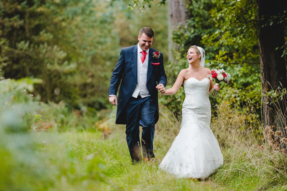 couple walking through woods laughing