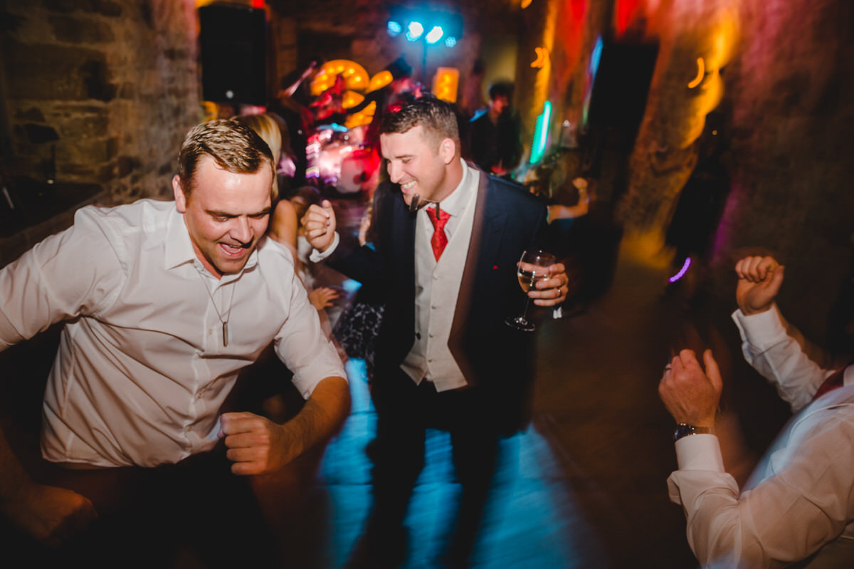 happy groom dancing at reception