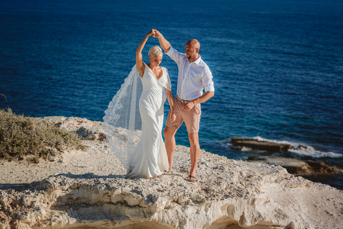 Bride and groom dance on the Cyprus cliffs in front of the turquoise blue sea