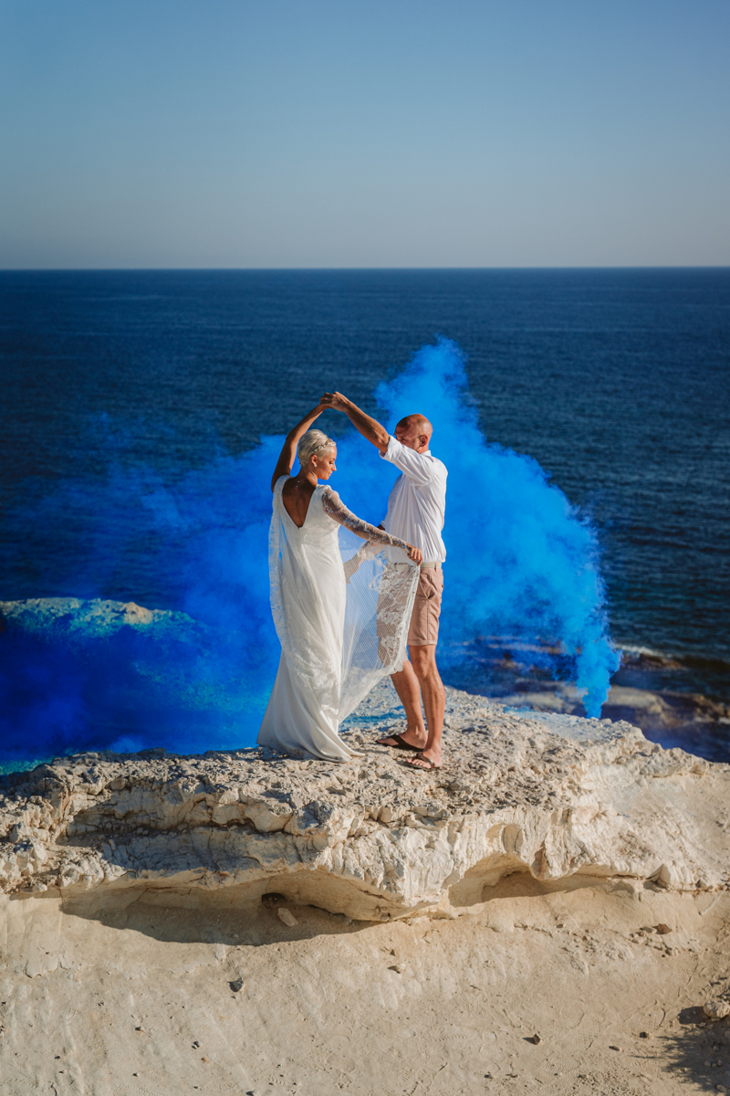 Blue flare adds drama to the couple's first dance on the rocks in Cyprus