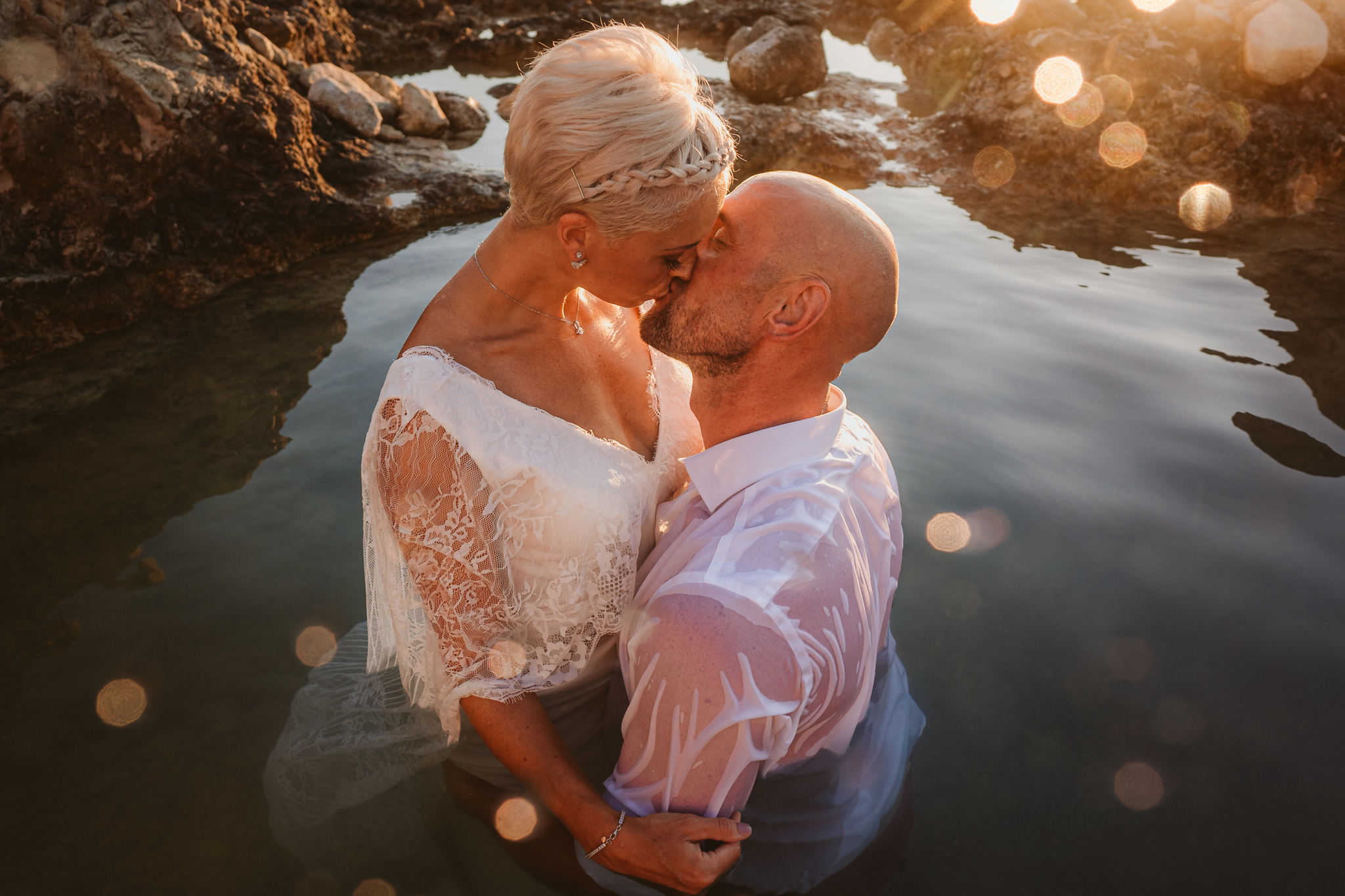 Bride and groom kiss in the water at sunset on their Cyprus sea caves trash the dress photoshoot