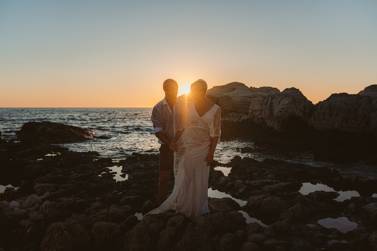 Bride and groom pose beside the Cyprus sea caves at sunset with their trash the dress photographer