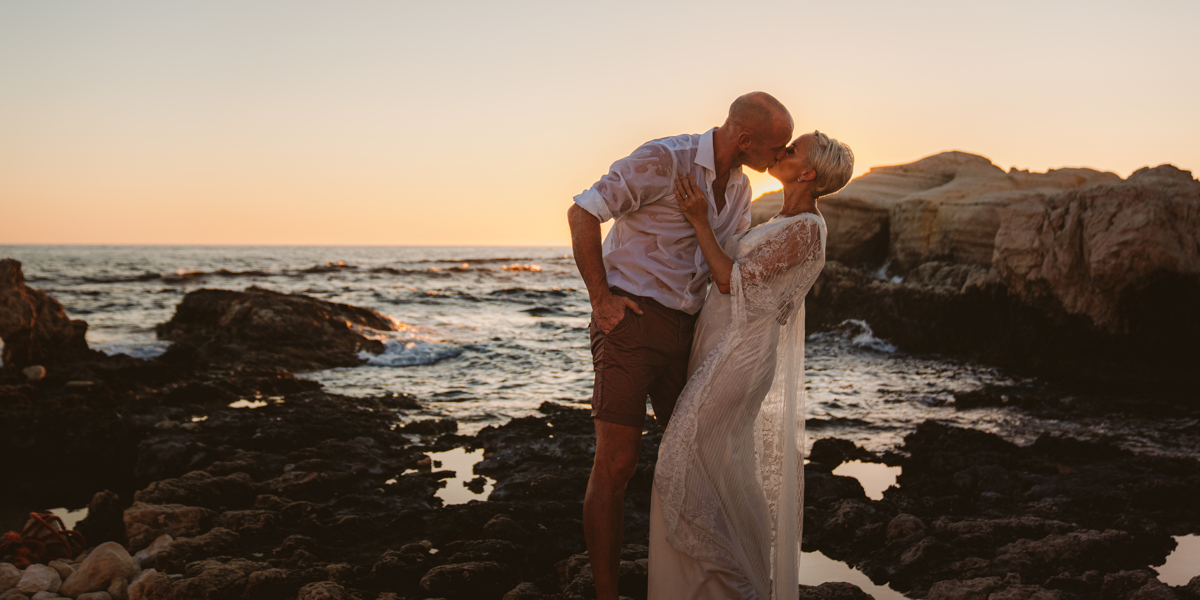 Newlyweds kiss and dip as the sun sets behind them, captured by their Cyprus sea caves wedding photographer