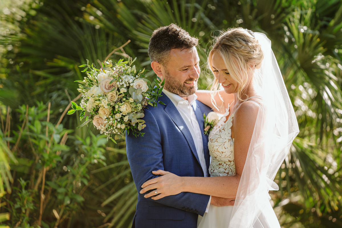 Can Gall Ibiza wedding photographer takes picture of couple embracing with bouquet