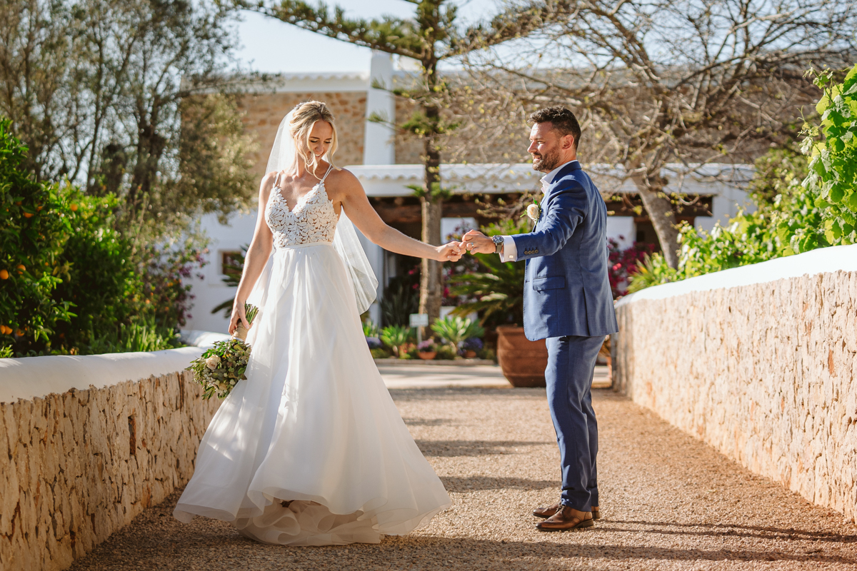 Can Gall Ibiza wedding photographer takes photo of bride and groom dancing on the pathway